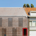 """In this Facade Focus on brick, Tom Verschueren, of Mechelen, Belgium-based DMVA Architects, created a closed street-side facade with an open backside facing the garden, totally glazed from the ground up to the saddleback roof. On the street side, the only true opening is the door; the seven tall, slim windows are screened by what Verschueren calls """"knitted"""" bricks. """"In this part of Belgium, 90 percent of the houses are built with brick,"""" says Verschueren. """"It's a classic material that we tried to use in House BVA in a totally different way."""""""