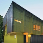 Tuned into its sylvan setting, this affordable green home in Hillsborough, North Carolina, is a modern take on the surrounding centuries-old structures. The house's skewed cubic form is clad in plank-like Cor-Ten steel panels and shielded by a rain screen. Over the years, the Cor-Ten will develop a rich patina that will liken the home to the weathered and rusted farm buildings in the area.