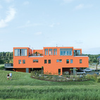 Seen here from the south, Villa van Vijven's orange facade is meant to mimic the tiled rooftops of Holland's country buildings, while the building's horizontal pull echoes the flat landscape. The second-floor living rooms look out on the 4,200-square-foot communal garden, one of only two shared spaces in the whole community.
