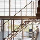 Seemingly a single, seamless unit, the stair is composed of two elements—treads and mezzanine—and held in place by two distinct strategies: The stairs are welded to, and cantilever out from, a series of steel tubes concealed in the walls; the mezzanine  is attached on one side to a steel beam, and hung at two other points from rods attached to the roof structure.