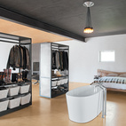 In the bedroom, an improbably placed tub is situated in front of two closets that can easily be maneuvered thanks to skateboard wheels affixed to the underside.  Photo by: Misty Keasler