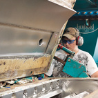 A worker operates the float-sink tank. Heavier, nonrecyclable materials sink to the bottom, leaving on the water's surface only rPET, which then becomes white rinse flake.