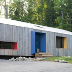 """When Jeff Taylor and Alex Miller designed the Pull House in Great Barrington, Massachusetts, they took """"form follows function"""" one step further: Form describes function. Along the house's facades, deep window openings pop through the silvery, white-cedar cladding in bright bursts. """"The punches of color are points of personal expression,"""" says Taylor, cofounder of Taylor and Miller Architecture and Design. """"They let the vitality of the residents leak out so passersby can experience the inside from the outside."""""""