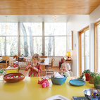 Hale's material preferences helped keep costs low: Inexpensive plywood lines the ceiling and cork covers the floors. He covered the kitchen island with yellow plastic laminate.  Photo by: Philip Newton
