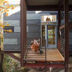 A porch at the bottom floor level serves as a rest space, play area, and work spot when Hale pulls out his tools. The horizontal window above connects the first floor to the deck so Hale and Edmonds can keep a watchful eye on the girls when they play outside.  Photo by: Philip Newton