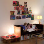 Back in the living room, the girls busy themselves with books. Hale designed and made the plywood couch with built-in book storage as well as the plywood-and-red-plastic-laminate side table. Hale's partner at Shed Architecture and Design, Thomas Schaer, created the Richlite-topped, steel-base coffee table.  Photo by: Philip Newton