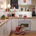 Pippa (left) and Maisie (right) play in the kitchen. Though Hale and Edmonds would have preferred Bosch appliances, a deal at Ikea was too good to pass up. They purchased all of the cabinets and appliances (a combination that earned them 20-percent off the total) for a mere $4,700.  Photo by: Philip Newton
