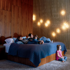 "Arbel's ""14"" sconces spot the wall to ethereal effect in the master bedroom. ""I wanted this place to be habitable. One of my greatest criticisms of modern architecture is that it often forgets to make things cozy.""Don't miss a word of Dwell! Download our  FREE app from iTunes, friend us on Facebook, or follow us on Twitter!   Photo by: Jason Schmidt"