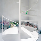 A steel spiral staircase efficiently links all three floors. With no interior doors, Yurika can keep an ear on the shop from upstairs while maintaining the privacy of her home with the help of the vertical distance.  Photo by: Takashi Homma