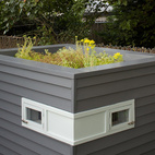 """Switching coasts from Brooklyn to Portland gave architects Mitchell Snyder and Shelley Martin a new set of unexpected clients: three young hens. Snyder finished the sleek-looking coop with reclaimed cedar siding and ventilated it with two upper windows. On top, he added a green roof: """"The living roof helps keep the coop cool, but mostly it was a chance to experiment and design something fun.""""  Photo by John Clark.   This originally appeared in Coop Dreams."""