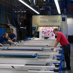 The more complex the design and the more colors used, the more plates—and hands (up to four professionals at a time)—are required to run the 80-foot-long printer.  Courtesy of 2011.