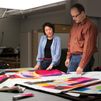 Studio member Eri Shimatsuka (left) and studio manager Petri Juslin (right) compare a first fabric proof to the artist's original drawing.  Courtesy of 2011                                                  .
