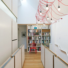 A dim Toronto Tudor gets an airy new look. The home's second-story hallway, which serves as an open office and library, was suffering from a severe lack of light. Lifting up one side of the old pitched roof made room for a linear skylight, which faces south to allow in as many rays as possible, and the modification transformed the top floor into a loftlike double-height space. Inexpensive detailing then added texture and scale: Simple plywood panels attached to cold-rolled-steel frames serve as guards along the stairs.  Courtesy of Copyright: Finn O'Hara.