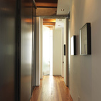 A long hallway from the living room separates the public and private sections of the home and extends the distance between the living quarters and work spaces.  Courtesy of justin fantl photography.