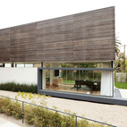 The larch rainscreen covering the second floor give the house a light appearance and also provides privacy. Though it's difficult for outsiders to look in, the openings between the slats of wood let the family sneak views to the outside.