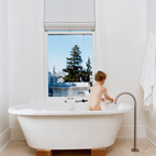 Jonathan Nelson's one wish for the master bathroom was for views from the Zuma tub. He got that and then some, and now three-year-old Jonas (pictured) and his older brother refuse to bathe anywhere else. The stand-alone faucet is by Lefroy Brooks from the XO collection.  Photo by: Dave Lauridsen