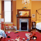 In the boys' shared room, Jasper finds plenty of space to scatter toys. An original chandelier provides a reminder of the house's past while muted orange walls plant it firmly in the present.  Photo by: Dave Lauridsen