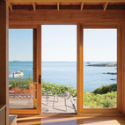 On an island 20 miles off the coast of Maine, a writer, with the help of his daughter, built not only a room but an entire green getaway of his own. The deck off the front of the sustainably built Porter Cottage is also minimally furnished with elegant lines of beach rock and two Leaf chairs by Arper.  Photo by: Eirik Johnson