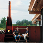 Sherbanuk (left) and Campbell sit by the outdoor fireplace, which adjoins the screened-in porch.