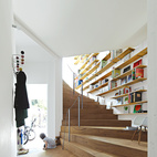A twisting staircase in this compact Japanese house offers a convenient way to reach books on an adjacent multi-tiered shelf.