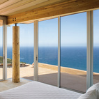 Architect Mary Ann Schicketanz created a 1,900-square-foot home in Big Sur, California, that hugs its hillside site. Here, two walls of floor-to-ceiling windows in the master bedroom frame expansive vistas of the Pacific Ocean. Take a peek through the glass at the green design features of this oceanside home.   Photo by: Robert Canfield