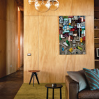"""O'Sullivan's blown-glass pendant lights make another appearance in the living area, where a kauri-plywood wall showcases a piece by artist Martin Poppelwell. An Ipsilon side table by Rodrigo Torres for Poliform rests beneath the artwork and a Jiff side table by Flexform sits next to the sofa. The patterned pillow is made from fabric from Jim Thompson's Illusion range, while the solid one is from Rubelli's James Dean range, both from Auckland's Atelier Textiles. """"Any colors that I brought into the house reflected the colors of the natural materials the architect had used,"""" says Jay. """"No hot pinks!"""""""