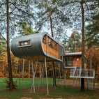 Design firm Baumraum's modern tree house in Belgium sparks a dialogue about nature and architecture. This 450-square-foot retreat, nestled between the limbs of pine and oak trees in northeastern Belgium. As a part of their green mission, the city of Hechtel-Eksel, the Flemish Forest and Nature Agency, paper company Sappi, and communications firm Proximity BBDO commissioned the structure clad in zinc and larch as a place for businesses to host sustainability oriented conferences.