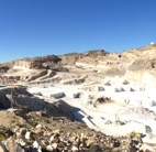 """Cosentino owns a lease to mine this mountain. Here, you can see the various layers of rock in the quarry. Through excavations, they've gradually excised portions until they hit the marble motherlode. The mine has been producing marble blocks for 40 years and has an expected lifespan of 40 more years. The trade name of the stone is """"Blanco Macael,"""" referring to the city from which the stone originates. It's one of the many varieties of natural stone the company distributes."""