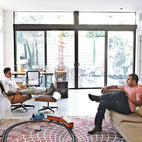 "A multi-generational home in San Diego, California, elegantly combines sustainability and luxury. Brothers Nima and Soheil relax in the family room on an Eames lounge chair and a custom sofa they designed. Of making decisions as a family, Soheil says with a laugh, ""sometimes it's about whoever gets to Mom and Dad first."" Photo by Ye Rin Mok.   Photo by: Ye Rin Mok"