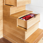 Steps leading to Michael Pozner's lofted bed in his modern Manhattan apartment offer storage for clothes.  Photo by: Raimund Koch