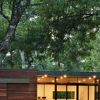 In a family's pint-size lake retreat in Austin, Texas, ipe siding and decking meet concrete floors and steel-and-glass windows. Stained cyprus was used for the ceiling and soffit. The custom barn-style sliding door conceals the family's collection of giant inner tubes and other boating equipment. Photo by Kimberly Davis.    This originally appeared in Small and Modern: A Family Lakeside Getaway in Texas.