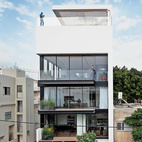 Tall and surprisingly open, the Tel Aviv Town House by Pitsou Kedem Architects continues in the tradition of its Bauhaus-inspired neighbors with a white facade and black window frames. Photo by Amit Geron.    This originally appeared in 5 Modern Courtyards Part Two .