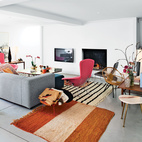 A pair of interior architects with a years-in-the-making furniture collection recast an old Belgian factory—in Bellem, a 25-minute drive out of Ghent and halfway to Bruges—as a playful family home. The stars of the living room are a pair of pink Bird chairs by Harry Bertoia for Knoll, accented by a brass-and-steel coffee table designed by homeowners as well as vintage marble-topped and wood occasional tables and antique rugs are from Morocco. Photo by Frederik Vercruysse.