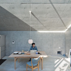Nakada works from an Alvar Aalto table in the living and dining area, adjacent to the kitchen. He saved on some elements, such as the plywood cabinetry, and splurged on others, such as the Finn Juhl chairs and Vilhelm Lauritzen lamp. A skylight beneath the angled roof allows in a sliver of constantly changing light.  Courtesy of Iwan Baan .