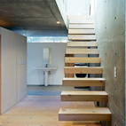 The staircase leads to the living area upstairs.  Courtesy of Iwan Baan .