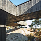 A section of the roof reaches over a rock outcropping—a detail that visually connects the house to the landscape and offers a handy way to climb up to the roof deck without using a ladder.  Courtesy of Ivan Brodey .