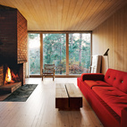 The interiors are clad in white-glazed pine, a contrast to the black-stained facade. The brick fireplace is original. Near a Polder sofa by Hella Jongerius for Vitra is a coffee table of Sævik's design. The rocking chair is vintage and came with the house.  Courtesy of Ivan Brodey .  This originally appeared in How to Design with Red.