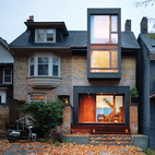 Mounted in a blackened steel frame, the wood front door to this home near Toronto, Canada, shines with a warm, burnished glow. The glass window just beside provides a promising glimpse of the domestic spaces just beyond. Photo by Shai Gil.  Photo by Shai Gil.