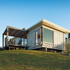 A compact prefab vacation home in the seaside community of Onemana Beach is clad in plywood and vertical timber battens finished in Resene's Lumbersider paint in Foam.  Photo by: Simon DevittCourtesy of: Simon Devitt
