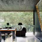 With his son, William, watching, architect Noah Walker tries out the floor-to-ceiling Schüco glass doors he integrated into a guesthouse he designed off an existing barn for Nathan Frankel, an amateur violinist, in Beverly Hills, California. The new portion features an open living-dining area. See more glass houses we love!  Photo by: José Mandojana