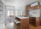 """A door frame was preserved as """"a sculptural memory piece,"""" Sara Imhoff says, after a wall separating the old kitchen from a small dining room was demolished. The countertops and backsplash are by Caesarstone.  Courtesy of Aaron Leitz."""