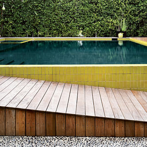 The final, layered look of the pool and its surroundings was completed—–with pain-staking precision—–in 2008. The tiles were custom designed with Mission Tile West to hit a pea-green hue and sized specifically to top the narrow walls. To create the seeded