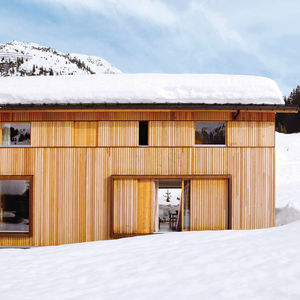 The house, which is gently pushed into the hillside, has a large basement holding a garage, ski room, storage areas, and utility spaces as well as the entrance hall.