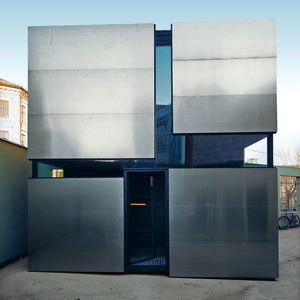 The metallic geometry of the Boxhome's exterior shines in confident contrast to the dark woods used indoors.