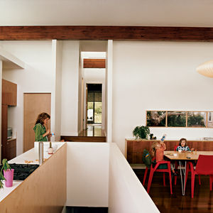 Michele eats lunch in the kitchen; a view of the central hallway and master bedroom lays beyond. Three-year-old Maple slurps from a water bottle with Judith, five, at the dining table, also built by Jamie. The Arco armchairs are by Mario Bellino for Helle