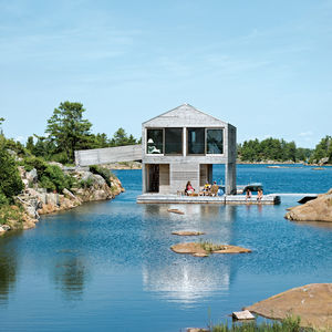 The Floating House rests in a cove on Beth and Doug Worple's horseshoe-shaped private island. Clad in raw cedar, it's a contemporary riff on the traditional boathouses found throughout the area—but simplified, as architect Michael Meredith puts it, into a