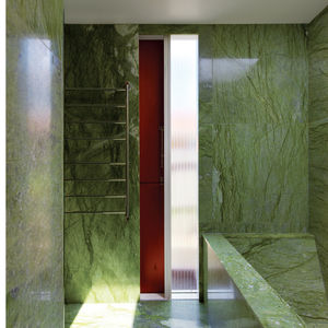 Modern bathroom clad in green Verde Ming marble
