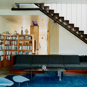 A built-in sofa with Design Tex upholstery marks the boundary between the two-level addition and the bungalow. Leading up to the master bedroom, a perforated metal staircase, lit from above, casts a Sigmar Polke–like shadow grid on the concrete floor.
