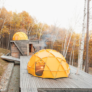 Yellow North Face tent atop a wooden deck