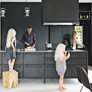 modern kitchen with black cabinets and white floor in Copenhagen